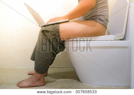 Using Laptop Computer On Toilet Or Restroom. The Asian Man Sitting In The Toilet And Working On The
