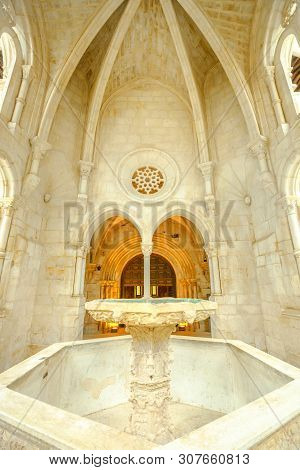Alcobaca, Portugal - August 15, 2017: A Stone Carved Gothic Fountain, Arches And A Rose Window In Cl