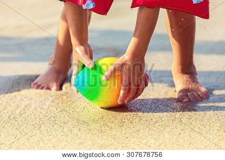 Baby Feet Walking On Sand Beach Grabbing Rugby Ball - Playful Toddler Wearing Inflatable Armbands Ha