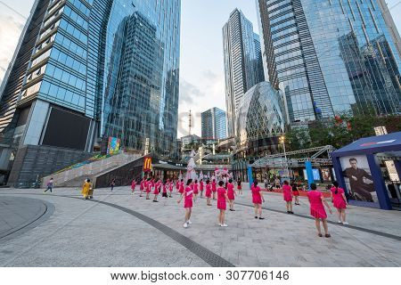 Chengdu, Sichuan Province, China - June 6, 2019 : Senior Women With Red Outfit Practising Square Dan
