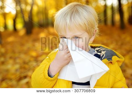 Little Boy Sneezing And Wipes Nose With Napkin During Walking In Autumn Park. Flu Season And Cold Rh