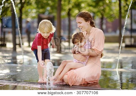 Mother With Disabled Girl And Boy Having Fun On Fountain At Sunny Summer Park. Child Cerebral Palsy.