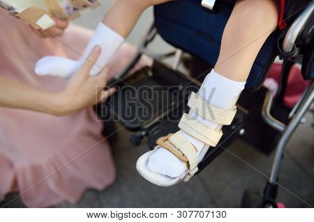 Mother Puts On Orthosis Her Daughter Legs. Disabled Girl Sitting On A Wheelchair. Child Cerebral Pal