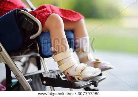 Disabled Girl Sitting In Wheelchair. On Her Legs Orthosis. Child Cerebral Palsy. Inclusion. Family W