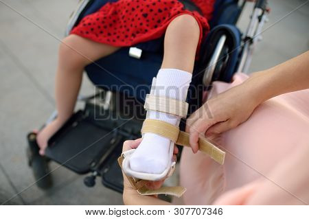 Mother Puts On Orthosis Her Daughter Legs Orthesis. Disabled Girl Sitting On A Wheelchair. Child Cer