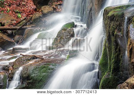 Close Up Details Of Waterfall Stream. Rapid Flow With Long Exposure. Wet Mossy Boulders. Fallen Foli