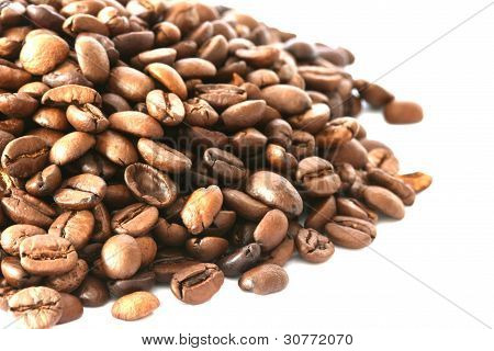 Whole coffee beans scattered on white background