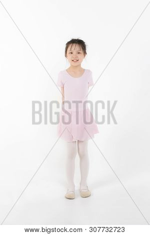Cute Pink Dressed Asian Girl In A Ballet Pose In Front Of Window. Concept For Sport And Perfomance A