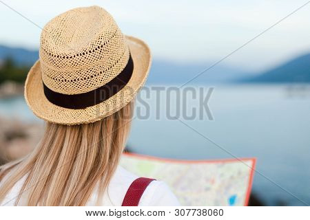 Traveler Is Looking At Map At Sea Beach. Woman Tourist Is Traveling. Girl In Straw Hat Is Enjoying S