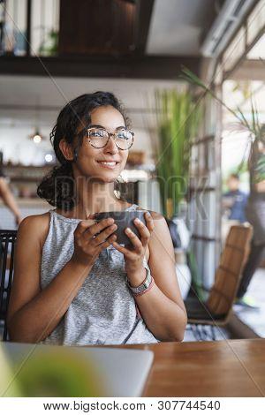 Vertical Shot Gentle Tender Relaxed Urban Girl Wear Glasses Enjoy Moment Sitting Alone Cafe Hold Cap