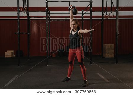 Young Woman Lifting A Heavy Weight Kettlebell At Gym. Caucasian Female Athlete Working Out At Gym. T