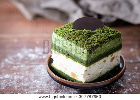 Macadamia cake with greentea and white cream on wooden table, close up, space to write. poster