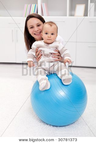 Baby gymnastic and fun with mother and large ball