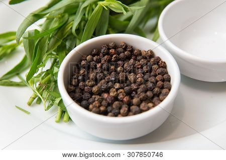 Black Pepper In White Bowl Over White Background . Saucer Dish With Black Pepper Peas Isolated On Wh