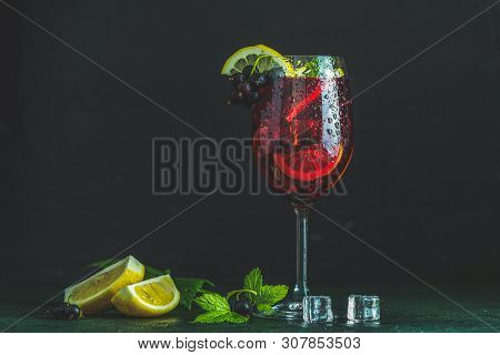 Cold Red Cocktail With Blackcurrant, Lemon, Mint And Ice In Tall Glass On Black Background. Summer D
