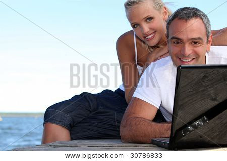 a couple on a pontoon near the sea, the man is doing computer,
