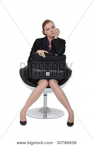 Austere businesswoman sitting in a chair with a briefcase on her lap