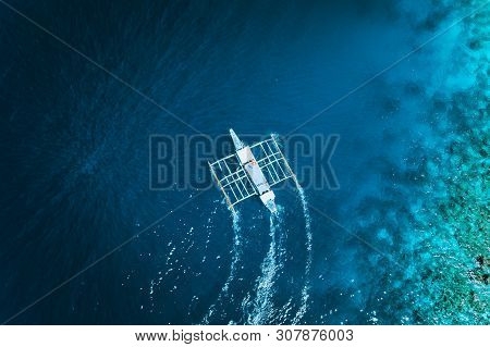 Aerial Drone View Of White Traditional Filipino Boat Floating On Top Of Clear Blue Water Surface. El