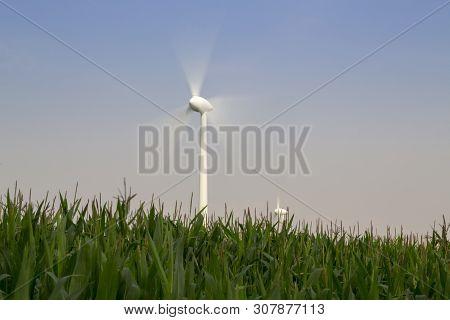 Long Exposure Of A Wind Wheel Standing In A Cornfield