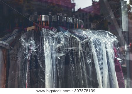 Clothes Wrapped With Plastic On A Rack In The Window Of A Laundry