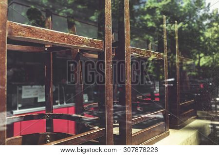 Old Chairs Of An Restaurant Stacked Behind A Window
