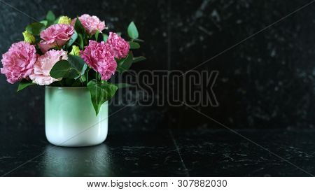 Black Marble Counter With Vase Of Pink Lisianthus Flowers With Copy Space.
