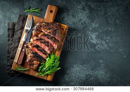 Sliced Steak Ribeye, Grilled With Pepper, Garlic, Salt And Thyme Served On A Wooden Cutting Board On