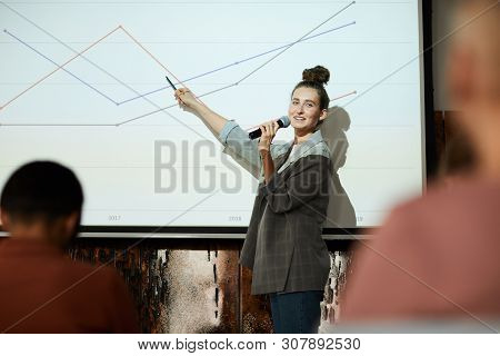 Waist Up Portrait Of Contemporary Businesswoman Giving Presentation Pointing At Graph Lines On Proje