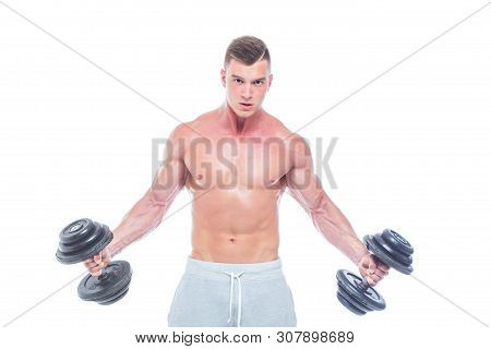 Handsome Power Athletic Man With Dumbbell Confidently Looking Forward. Strong Bodybuilder With Six P