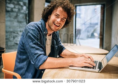 Portrait Of Happy Young Man With Curly Hair Using Laptop For Working And Browsing Online. Smart Cauc