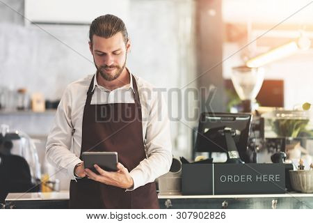 Male Barista Holding And Looking At Digital Tablet At The Coffee Shop Or Restaurant Cafe. Startup Of