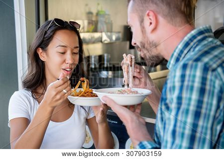 Young Interracial Couple Enjoying Eating Pasta From Food Truck