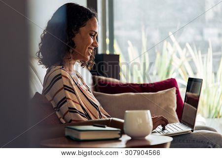 Young Woman Sitting On The Couch Working On Laptop. African Female Working On Laptop Computer At Hom
