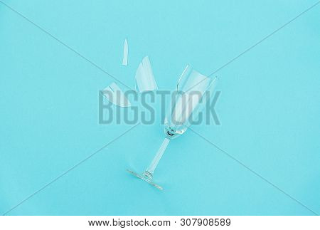 Broken Champagne Glass With Splinters On Blue Background With Copy Space. Concept Fight Against Alco