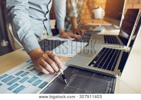 Software Developer Is Pointing To The Paper Working And Analyzing Together The Code Written Into The