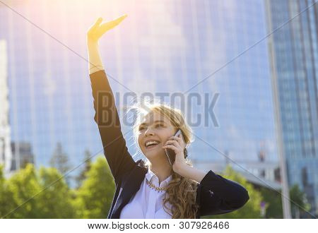 Young Happy Businesswoman With Raised Arm Talking On Phone At Street Receiving Good News. Lady With