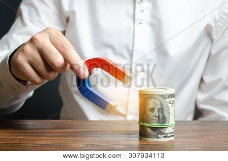 Businessman Attracts Money With A Magnet. Attracting Money And Investments For Business Purposes And