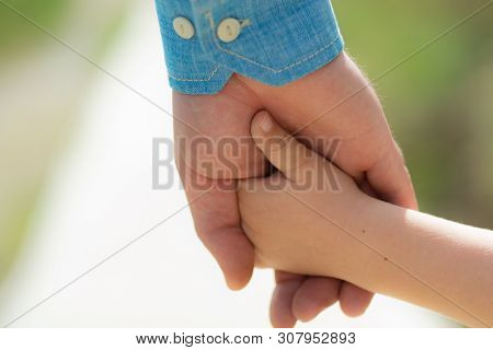 Family. Little Child Holding Hands With His Father Outdoors, Closeup. Family Time. Closeup Of Two To