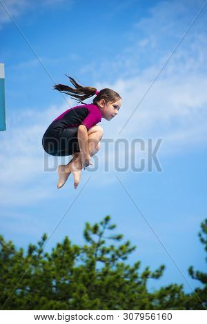 Little Caucasian Female 8 Years Old Girl In Neoprene Shorty Surfing Wetsuit Jumping From 5 Mether Di