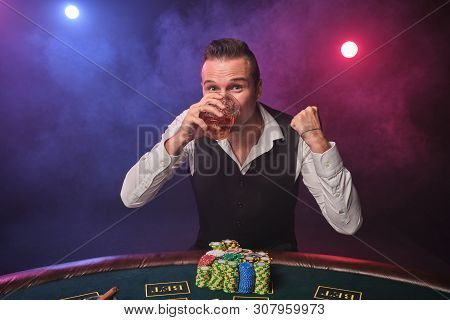 Wealthy man is posing at a poker table with chips and a glass of whiskey on it at a casino. poster
