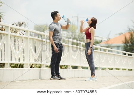 Thirsty sportsmen drinking fresh water after jogging in the morning poster