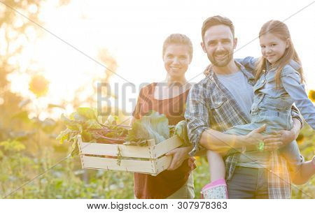 Portrait of smiling family with vegetables in crate at farm