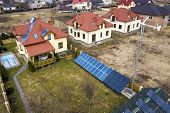 Aerial top view of residential area with new houses with roof solar photo voltaic panels, wind turbine mill and stand-alone exterior solar panel systems. Renewable green energy generation concept. poster