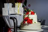 closeup two-tiered cake with roses on glass tray against gifts poster