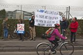 EXETER - MARCH 7:  A cyclist travels past a sign that has a quote from Aneurin Bevan, who spearheaded the establishment NHS, during the NHS reform protest outside the Royal Devon & Exeter Hospital on March 7, 2012 in Exeter, UK poster