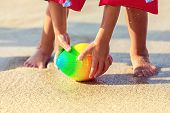 Baby feet walking on sand beach grabbing rugby ball - playful toddler wearing inflatable armbands hand holding ball from water in summer vacation - Children stand barefoot on sand poster