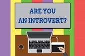 Text sign showing Are You An Introvertquestion. Conceptual photo demonstrating who tends to turn inward mentally Upper view laptop wooden desk worker drawing tablet coffee cup office. poster