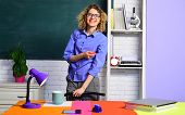 Smiling teacher in classroom. Young female teacher. Young teacher in glasses over green chalkboard background. Teacher with marker. poster