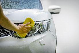 Hand With Yellow Sponge Washing Car Headlight