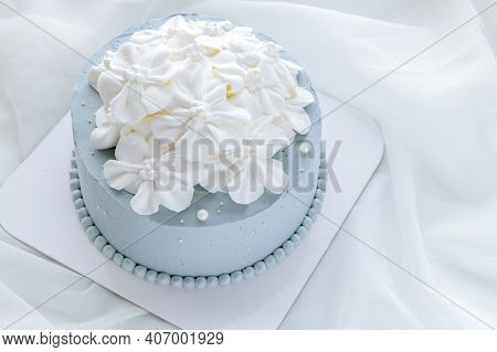 Pastel Blue Coconut Cake Decorated With White Flowers From Fresh Cream On White Cloth.  Homemade And